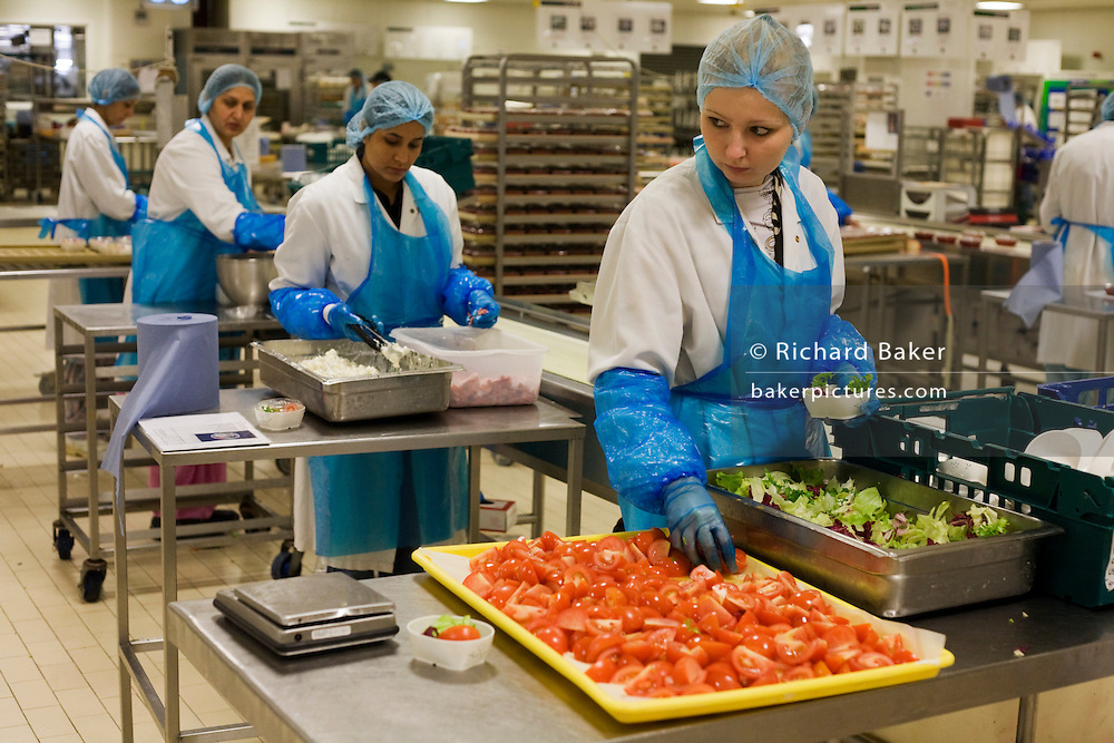 "A production line of lady employees from the world's largest independent provider of airline catering and provisioning services, Gate Gourmet, prepare salad trays in the company's factory on the southern perimeter road at Heathrow Airport, West London. Gate Gourmet serve more than 200 million meals on 2 million airline flights a year to their 250-plus airline customers at more than 100 airport locations around the globe. Apart from creating the bespoke meals for an airline's culture and ethnic demands, that pack the pre-flight carts, deliver and load into the aircraft galleys and afterwards, they dispose of the waste and strip, wash and sterilize the equipment. From writer Alain de Botton's book project ""A Week at the Airport: A Heathrow Diary"" (2009). ."