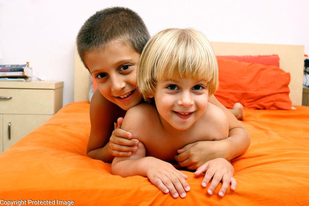 Brothers on bed, Modiin, Israel. Photography by Debbie Zimelman, Modiin, Israel