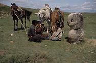 Mongolia. stone statue (Turkish 6th century)  Tarnai Gol       / Jeunes cavaliers devant une statue monolythique. / Lieu de rendez-vous idéal, cette statue de l'époque des Turcs Célestes (VI-VIIIème siècles) offre un point de repaire précis dans la steppe infinie. L'idole de pierre (KUN TCHULUU) semble être assise en tailleur. Elle a le bras droit, plié au niveau du coude et tient probablement une coupe, tandis que la main gauche, au niveau de la ceinture, empoigne sans doute un poignard. Décapitée, peut-être par les conquérants successifs des steppes, ce genre de statue était érigée à la surface d'une tombe d'un noble guerrier. Elle a peut-être un rapport avec le tumulus situé à l'extrème gauche. Quoiqu'il en soit, personne aujourdh'hui n'est en mesure de reconnaître les personnages en question. (Bord de la rivière TARNAI GOL, dans l'aymag de BULGAN  / /20    L920731a  /  P0002626