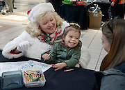 gbs120416c/ASEC -- Isabel James, 3, smiles at her mom, Jacklyn Herrman of Albuquerque, while sitting on the lap of Mrs. Claus, aka Loretta Curtis of Rio Rancho, during the Sensitive Santa event at Cottonwood Mall on Sunday morning, Dec. 4, 2016. The RSVP event before regular mall hours provided children with special needs and their families with a sensory friendly environment to safely experience the tradition of visiting Santa Claus. (Greg Sorber/Albuquerque Journal)