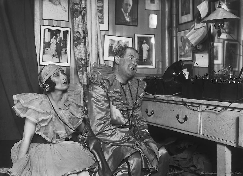 "Betty Chester and Davy Burnaby, stars of the variety show ""The Co-Optimists,"" listen to an early wireless set with headphones, 1923"