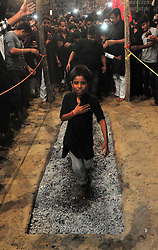 October 28, 2016 - Allahabad, Uttar Pradesh, India - Allahabad: A minor Shia Muslim devotee walks on cinder/anagar as they take part in a mourning procession during Muharram in Allahabad on 28-10-2016, Muharram is celebrated to mark the climax of the mourning which is Called Ashura, The ccommenmoration of Imam Hussain's. photo by prabhat kumar verma (Credit Image: © Prabhat Kumar Verma via ZUMA Wire)