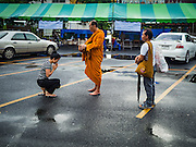 07 AUGUST 2016 - BANGKOK, THAILAND:  A Buddhist monk accepts alms from a woman in front of a polling place at Wat That Thong in Bangkok. The green awning covers the voting booths. Monks are not allowed to vote in Thai elections. Thais voted Sunday in the referendum to approve a new charter (constitution) for Thailand. The new charter was written by a government appointed panel after the military coup that deposed the elected civilian government in May, 2014. The charter referendum is the first country wide election since the coup.      PHOTO BY JACK KURTZ