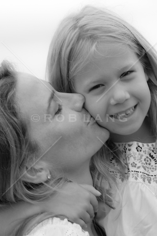 woman kissing the cheek of a little girl