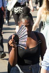 © Licensed to London News Pictures. 24/07/2018. London, UK.  A woman with a fan as commuters walk to work over London Bridge during another day of hot and sunny weather in the capital.  Photo credit: Vickie Flores/LNP