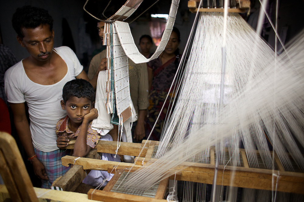 A boy and his father, a weaver, beside a hand-loom in the village of Kothakota which is known for its fine silk saris. Once forced into selling their fine silk-saris at a reduced-rate to the agents that supplied the silk thread, hand-loom workers in Mahaboobnagar District are now able to access loans through their local SHGs and invest in the costs of production themselves. This allows weavers to choose to whom they sell their saris and so guarantee a higher return for their labour. The Samista Handlooms store run by Adarsa Mahila Sahakara Samikhya (AMSS) only charges weavers a ten-percent commission rate on sales of their saris. <br /> <br /> Adarsa Mahila Sahakara Samikhya (AMSS) is a federation of women's Self Help Groups (SHGs) established in 1996 in Mahaboobnagar District in Andhra Pradesh. Since that time, AMSS's membership has grown from 2,500 to 8,600 women. AMSS is made up of an elected management committee which meets at their resource centre in the village of Moosapet. The AMSS resource centre provides training facilities for the 569 SHGs it represents. The resource centre also offers loans at nominal rates of interest together with a nursery facility, a restaurant business and a hand-loom store selling the work of local weavers. <br /> <br /> Photo: Tom Pietrasik<br /> Andhra Pradesh. India<br /> August 25th 2010