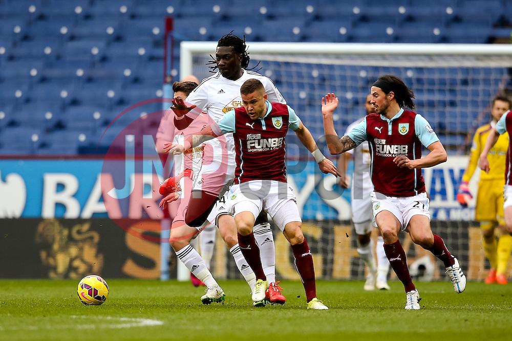 Burnley's Michael Kightly challenged by Bafetimbi Gomis of Swansea City - Photo mandatory by-line: Matt McNulty/JMP - Mobile: 07966 386802 - 28/02/2015 - SPORT - Football - Burnley - Turf Moor - Burnley v Swansea City - Barclays Premier League