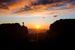 © Licensed to London News Pictures. 03/04/2019. Ilkley UK. A walker stands on top of the Cow & Calf rocks as the sun rose this morning in Yorkshire. Photo credit: Andrew McCaren/LNP