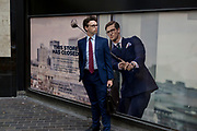A businessman pauses next to a closed shop poster featuring a similar man also wearing a blue suit - a favoured style and colour of menswear in the City of London, the capital's financial district - aka the Square Mile, on 29th August 2018, in London, England.