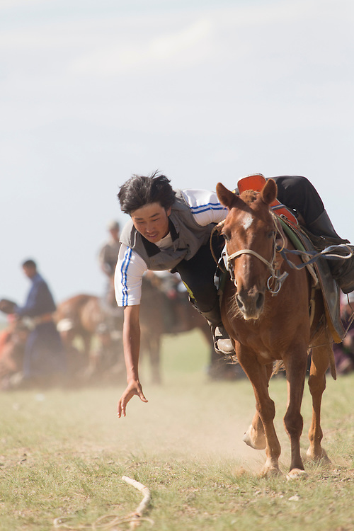 A young Mongolian man leans over his horse attempting to grab a wooden switch off of the ground while riding at a full gallop after the Naadam Festival at the Three Camel Lodge in the Gobi Desert of Mongolia on July 31, 2012. Horsemanship is very important to the Mongolian culture and this extra-festival sport has grown out of the fact that horse racing is considered one of the ?Three Manly Sports? practiced during the Naadam Festival. © 2012 Tom Turner Photography