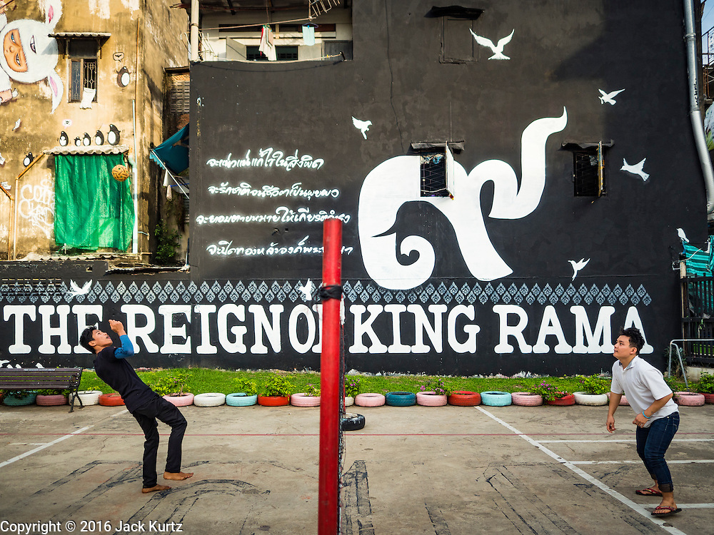"01 DECEMBER 2016 0 BANGKOK, THAILAND: Men play takraw in Chalermla Park (Graffiti Park) in Bangkok. The east wall of the park was repainted with a large mural that says ""Born in the reign of King Rama 9,"" with the nine written in Thai script. Bhumibol Adulyadej, the Late King of Thailand, was known as Rama 9. The park was repainted in his honor after his death on Oct 13.    PHOTO BY JACK KURTZ"