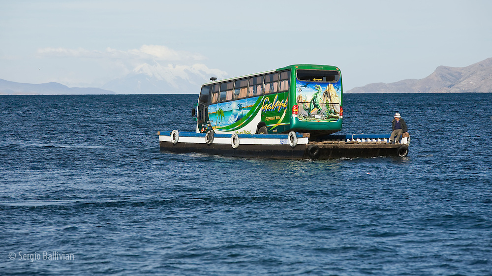 Vehicles cross the  Straits of Tiquina on Lake Titicaca in Bolivia.  Crude barges are used to take passengers, small vehicles and large buses  that are powered by small outboard motors across the 1 kilometer narrows on the Peninsula of Copacabana.