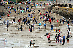"© Licensed to London News Pictures. 30/08/2014<br /> Gold diggers are still out digging for gold at Outer Harbour Beach in Folkestone,Kent at 7pm tonight (30.08.2014). <br /> £10,000 of buried treasure at Outer Harbour beach near Sunny Sands, Folkestone,Kent.<br /> The installation, entitled ""Folkestone Digs"", is funded by Bristol-based designers Situations and the idea for the project came from Berlin-based artist Michael Sailstorfer.<br /> The small gold bars - similar to a dog tag - come in two sizes, worth around £250 and £500.<br /> <br /> (Byline:Grant Falvey/LNP)"