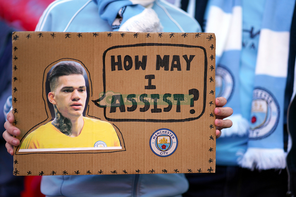 A Manchester City fan holds up a banner in the stands featuring Manchester City goalkeeper Ederson reading 'How may I assist?'