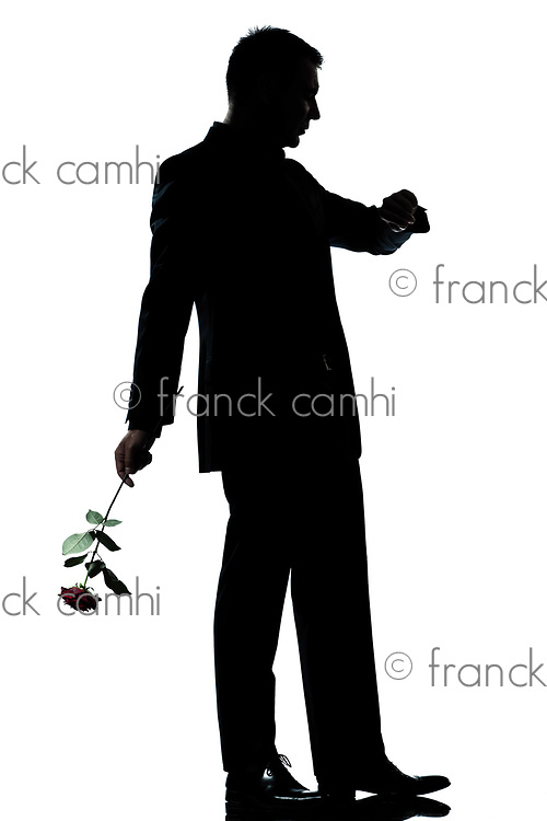 one caucasian man holding a rose flower  waiting checking time full length silhouette in studio isolated white background