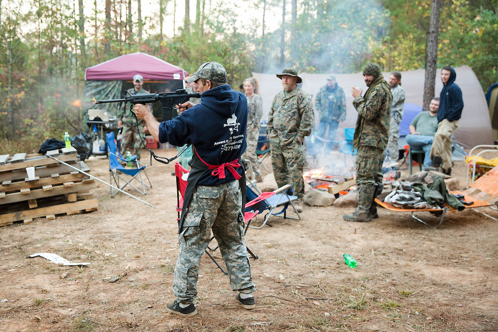 """Militia members from the several states, all of whom identify as part of the III% movement, gather near Jackson, Ga. on Saturday, Oct. 29, 2016 for training exercises. Here, wearing his cooking apron, Jason Thomas, also known as """"Blackout"""", shoots a rifle early in the morning. Mr. Thomas is a member of Georgia Security Force III% and was the cook for the event. Photo by Kevin D. Liles for The New York Times"""