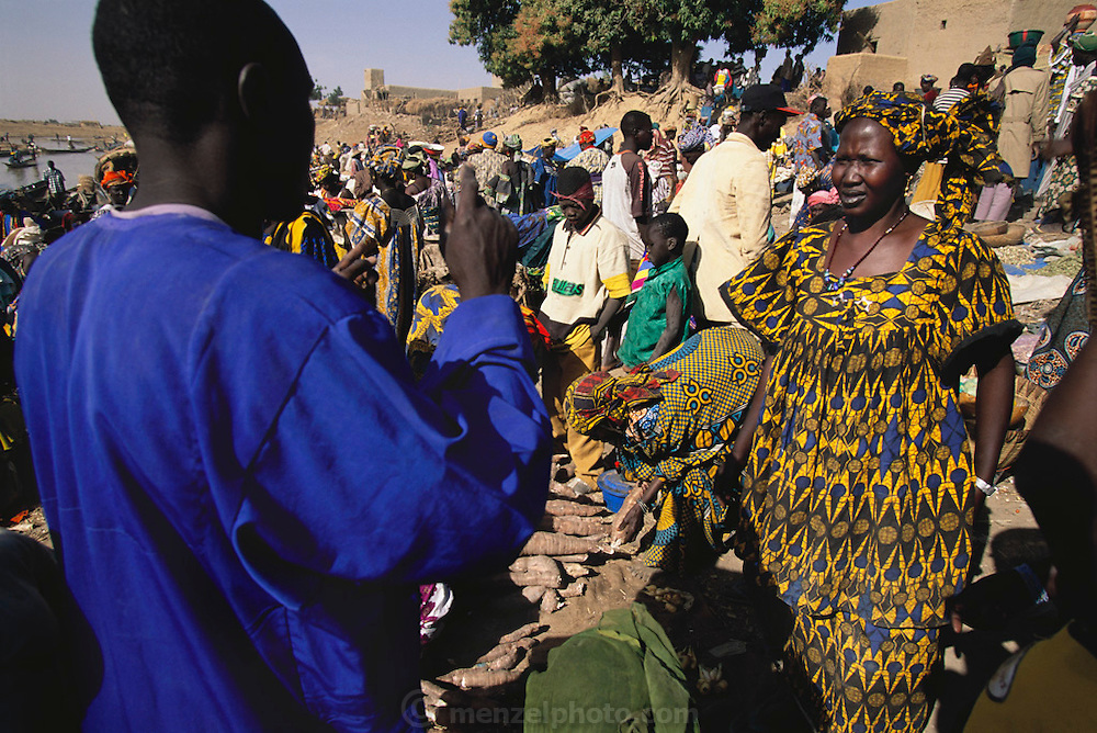 Grain trader Soumana Natomo and his second wife Fatoumata Toure discuss purchases and sales at the Saturday weekly market in their village of Kouakourou, Mali. Material World Project.