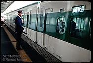 Stationmaster waits for bullet train (Shinkansen) to go after closing its doors; Utsunomiya. Japan