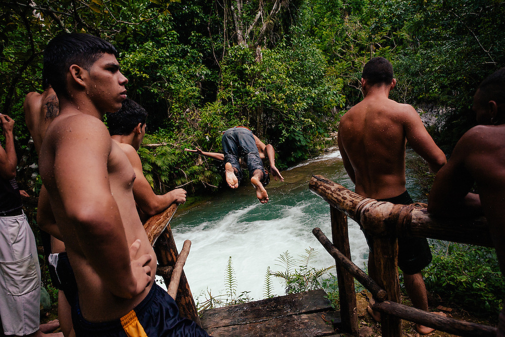Young boys amuse themselves diving off a platfrom in river rapids, Cuba.