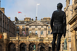 Silhouette of statue of James Braidwood Father of the British Fire Service with Edinburgh City Chambers on the Royal Mile to rear in Edinburgh Old Town, Scotland, UK