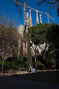 Tourists near the Sagrada Familia. ]Sagrada Familia, Barcelona is a massive unfinished church, designed by Antoni Gaudi, in central Barcelona. The building was started in 1882, but when this photograph was made in March 2018, with forcastes for completion set around 2030.