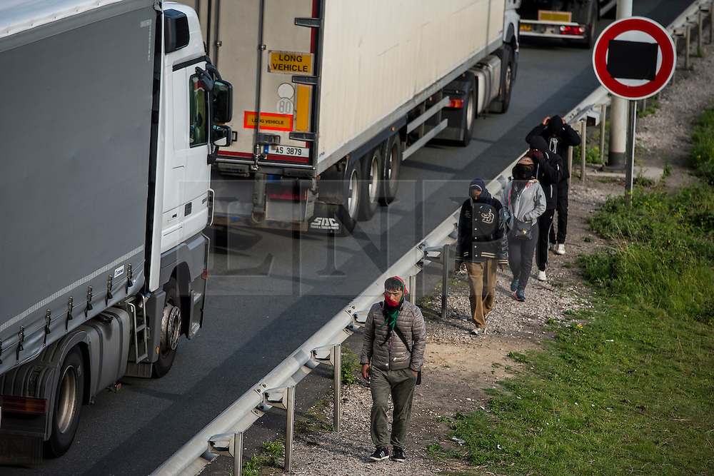 © London News Pictures. Calais, France. A group of immigrants watch over lorries as they queue to enter Eurotunnel at Calais.  Migrants attempting to reach the UK via the Eurotunnel at Calais in France. The situation has reached crisis point, which French police over run by attempts to cross the border. Photo credit: Ben Cawthra /LNP