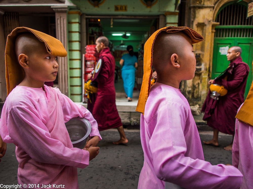 """03 NOVEMBER 2014 - YANGON, MYANMAR:  Buddhists """"nuns"""" on their morning alms rounds in Yangon, Myanmar. Nuns in the western sense don't exist in Myanmar, the girls are not actually ordained as nuns. Most come from very poor families. In some cases, their families couldn't afford to keep the girls so they were sent to live in religious environment. The girls will never be ordained as either monks or nuns, but they live a spiritual life, studying Buddhist theology and meditation and doing good deeds. In turn they are supported by their communities.    PHOTO BY JACK KURTZ"""
