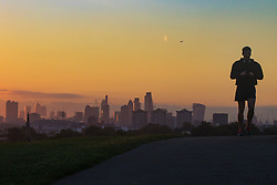 Primrose Hill, London, October 4th 2016. A runner's figure makes a silhouette on Primrose Hill as dawn breaks across London.