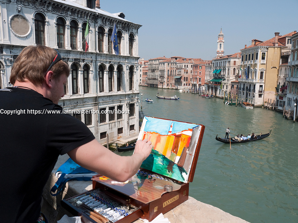 Artist painting scene beside Grand Canal in Venice