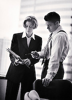Businesspeople looking at papers in office (B&W, soft focus)