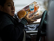"""26 MARCH 2020 - DES MOINES, IOWA: A parent picks up hot meals distributed by the school district at Weeks Middle School. Des Moines Public Schools (DMPS) started distributing hot lunches Thursday, the first day students were supposed to return to school. Schools will now remain closed until 13 April. Meals were distributed with """"social distancing"""" in mind. On Thursday morning, 24 March, Iowa reported 175 confirmed cases of the Coronavirus (SARS-CoV-2) and COVID-19. Restaurants, bars, movie theaters, places that draw crowds are closed until 07 April. The Governor has not ordered """"shelter in place""""  but several Mayors, including the Mayor of Des Moines, have asked residents to stay in their homes for all but the essential needs. People are being encouraged to practice """"social distancing"""" and many businesses are requiring or encouraging employees to telecommute.         PHOTO BY JACK KURTZ"""