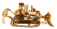X-ray image of a bulldozer (orange on white) by Jim Wehtje, specialist in x-ray art and design images.
