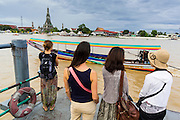 """23 SEPTEMBER 2013 - BANGKOK, THAILAND:  Tourists wait to catch a ferry to take them across the Chao Phraya River in Bangkok to Wat Arun on the last day the world famous stupa at the temple is open to the public. The full name of the temple is Wat Arunratchawararam Ratchaworamahavihara. The outstanding feature of Wat Arun is its central prang (Khmer-style tower). The world-famous stupa, known locally as Phra Prang Wat Arun, will be closed for three years to undergo repairs and renovation along with other structures in the temple compound. This will be the biggest repair and renovation work on the stupa in the last 14 years. In the past, even while large-scale work was being done, the stupa used to remain open to tourists. It may be named """"Temple of the Dawn"""" because the first light of morning reflects off the surface of the temple with a pearly iridescence. The height is reported by different sources as between 66,80 meters and 86 meters. The corners are marked by 4 smaller satellite prangs. The temple was built in the days of Thailand's ancient capital of Ayutthaya and originally known as Wat Makok (The Olive Temple). King Rama IV gave the temple the present name Wat Arunratchawararam. Wat Arun officially ordained its first westerner, an American, in 2005. The central prang symbolizes Mount Meru of the Indian cosmology. The temple's distinctive silhouette is the logo of the Tourism Authority of Thailand.          PHOTO BY JACK KURTZ"""