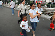 23 October 2007 - Guangzhou, China - A Chinese nanny looks after two young African children whilst their parents work. By some estimates over 10,000 Africans from many different nations live and pass through Guangzhou which has overtaken Hong Kong as the new hub for African businessmen looking to cut out the middle man. Some come for a few weeks, others years. These African traders, most of whom come from West African nations like Ghana, Togo and Nigeria, profit by purchasing cheap goods direct from Chinese factories and then sending them back to their home countries where they can be sold at higher prices. Photo Credit: Luke Duggleby