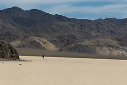 Adult male photographer carrying equipment across the Racetrack Playa, Death Valley National Park, California, United States of America