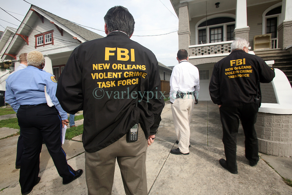 26 Jan 2012. New Orleans, Louisiana USA. .NOPD homicide detectives and the FBI's  Violent Crime Task force arrive at the scene of an attempted car jacking turned homicide to canvas the local area. The previous day (Jan 25th), local man Harry 'Mike' Ainsworth attempted to thwart a carjacking in progress having just dropped his children, ages 9 & 10 at the school bus stop. The carjacker shot Ainsworth twice through the windshield and fled the scene on foot. Mr Ainsworth's children witnessed their father's shooting. He stumbled onto a nearby front garden where he collapsed and died, held by his sobbing, screaming children.  .Photo; Charlie Varley