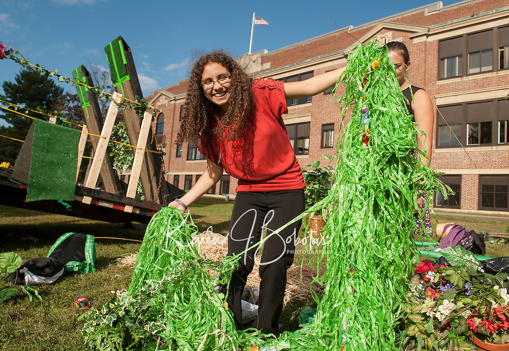 "Nickki Fain decorates the LHS Sophomore float ""Green"" on Thursday afternoon to represent the United Nations Environmental Program for the ""Colors For A Cause"" Homecoming theme  parade.     (Karen Bobotas/for the Laconia Daily Sun)"