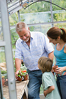 Family with boy planting flowers in greenhouse