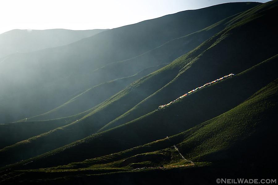 Tibetan Buddhist prayer flags blow in the wind on a mountains side near Yushu, Tibet.