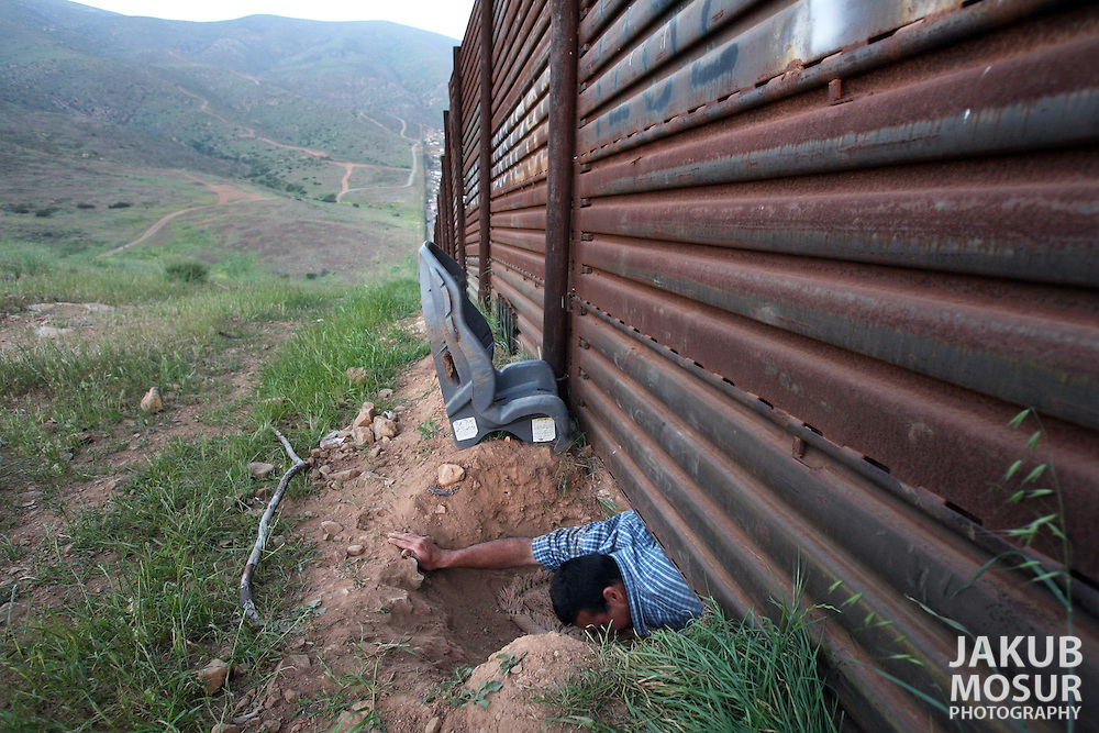 Ismael Castaeda, 23 from Mexico, crawls through a whole under the wall separating Mexico and the United States east of the Otay Mesa international border crossing in San Diego..Event on 5/5/06 in San Diego...JAKUB MOSUR / The Chronicle