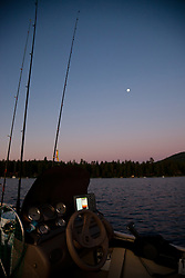 """""""Sunrise Fishing on Lake Tahoe 3"""" - These fishing poles and fishing boat were photographed at sunrise on Lake Tahoe. A full moon can be seen in the distance."""