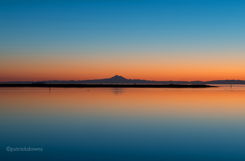 Dawn over Dungeness lagoon, with the tip of the Spit and Mt. Baker in the distance. The lighthouse beacon shines as a ship passes behind it.