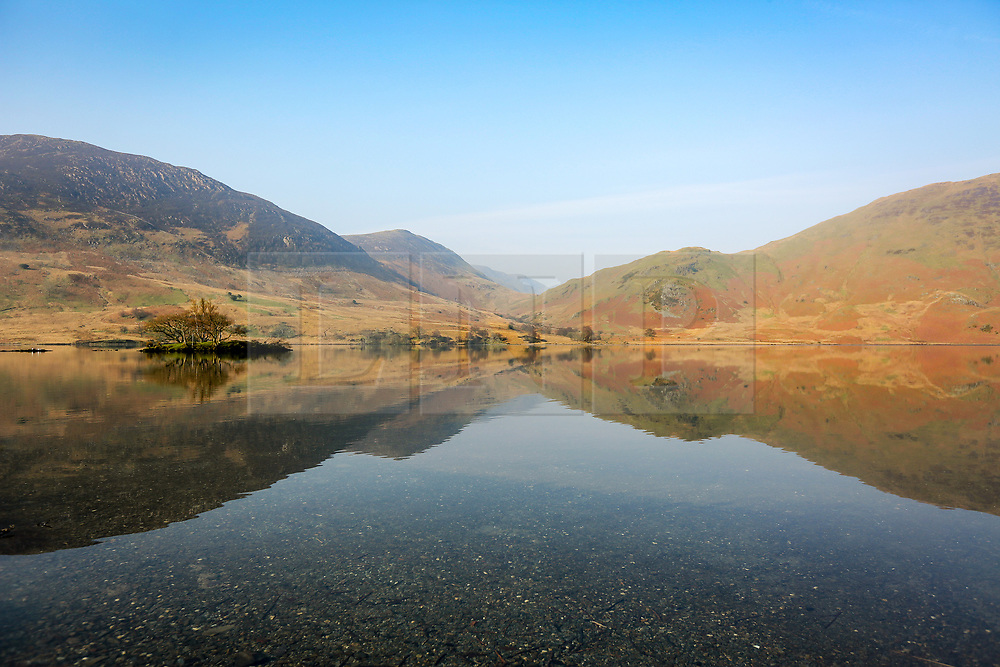 © Licensed to London News Pictures. 28/03/2017. Buttermere UK. The mountains that surround Crummock Water reflect in the calm water on another sunny day in Cumbria. Photo credit: Andrew McCaren/LNP