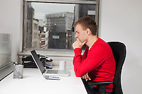 Side view of young man using laptop at desk in office