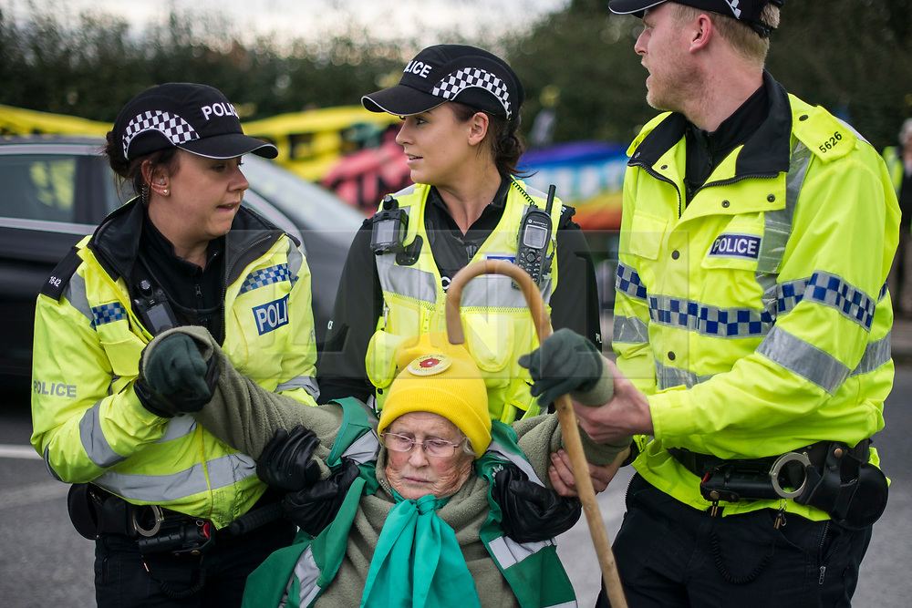 © Licensed to London News Pictures. 09/10/2017. Lancashire, UK.  Green Party member and anti-fracking activist Anne Power, 81, is removed by police after her sit down demonstration at the Anti-Fracking Demonstration on Preston New Road Lancashire. The protest blocked the entrance to Cuadrillas Hydraulic fracking site as part of a Demo that  brought together activists from Greenpeace, The Green Party and the local community to protest against the drilling taking place at the site.  Photo credit: Steven Speed/LNP