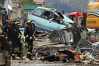 Rescue workers walk past  damaged car amongst fallen debris in the City Centre after a Powerful earth quack ripped through Christchurch, New Zealand on Tuesday lunch time killing at least 65 people as it brought down buildings, buckled roads and damaged churches and the Cities Cathedral. Photo Tim Clayton