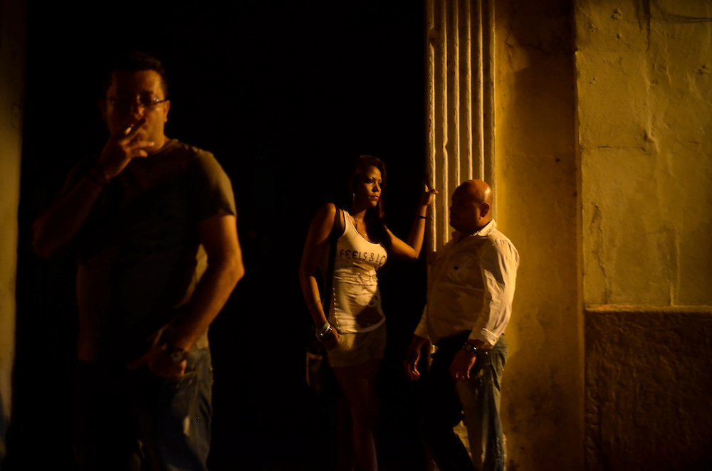 A woman and men stand outside of Club Elektra, a club where men go to pick up prostitutes in the historic district in Cartagena, Colombia.  A sex scandal erupted recently when secret service agents were found bringing prostitutes to their hotel rooms while in Cartagena preparing for President Barack Obama's arrival to the Summit of the Americas.