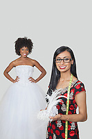 Indian female fashion designer holding feather fascinator with African American bride standing against gray background