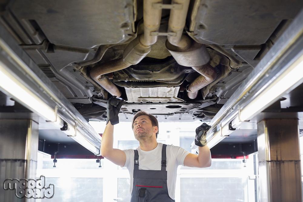 Mid adult male repair worker repairing car in workshop