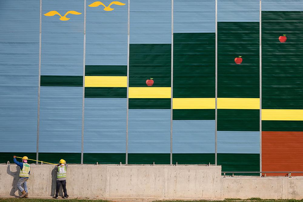 Workmen pass construction hoarding at KK Women's and Children's Hospital, Singapore.